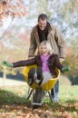 man-pushing-wife-in-wheelbarrow-199x300